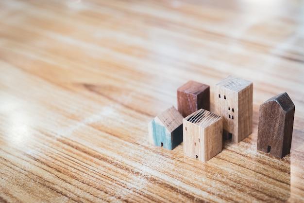Model domu z drewna na tle drewna, symbol budowy