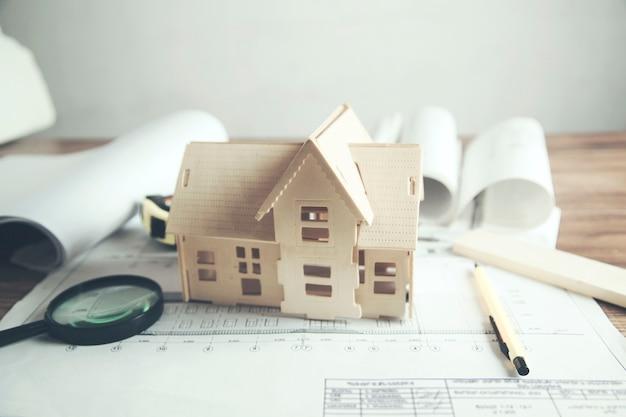 Model domu z lupą na stole