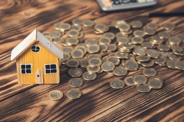 Model domu z monetami i kalkulatorem na stole. obsługa pośredników w obrocie nieruchomościami