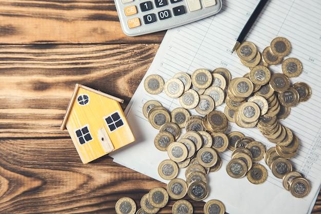 Model domu z monetami na dokumencie i kalkulatorze