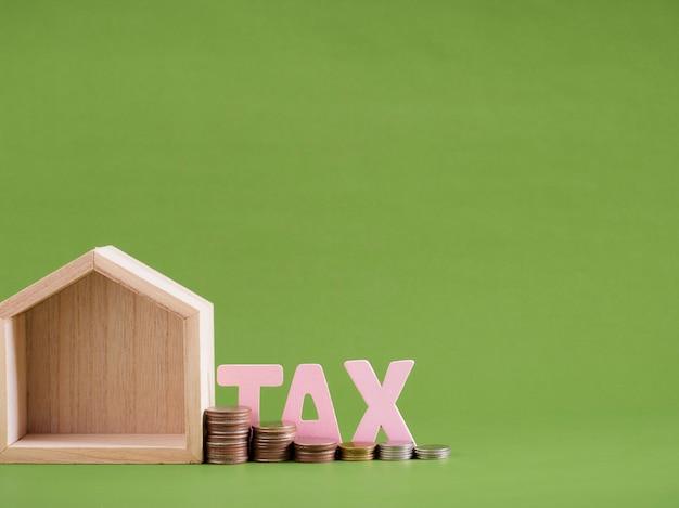Model domu z podatkiem słowo i monet na zielonym tle. miejsce na tekst