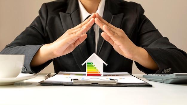 Model domu z wykresami oszczędzania energii i czystej energii w rękach biznesowych