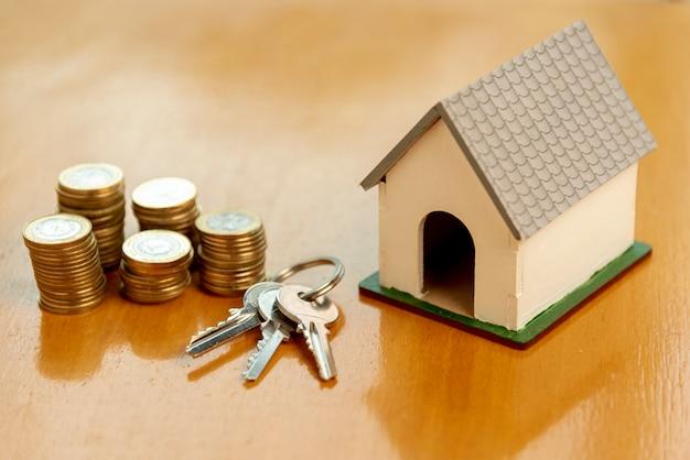 Model domu zabawki i stosy monet widok z przodu