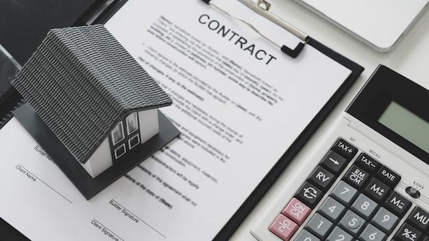 Model domu założył dokumenty kontraktowe z kalkulatorem i laptopem. ,kontraktowanie koncepcji budowy domu,strzał z góry.