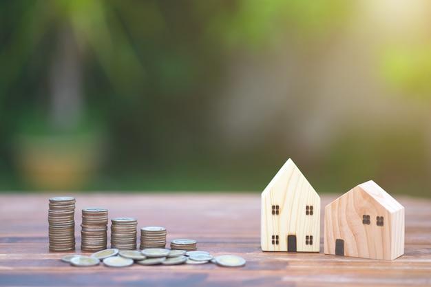 Model domu ze stosem monet pieniędzy