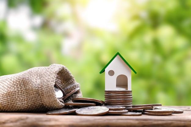 Model domu znajduje się na stosie monet z rozmytym zielonym naturalnym tłem pożyczki pod zastaw domu