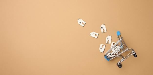 Model drewnianego domu i metalowego miniaturowego koszyka na jasnobrązowym tle, widok z góry. koncepcja wyszukiwania domu do wynajęcia, zakupu, hipoteki