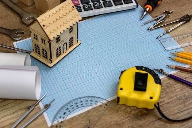 Model drewnianego domu na papierze milimetrowym z różnymi narzędziami