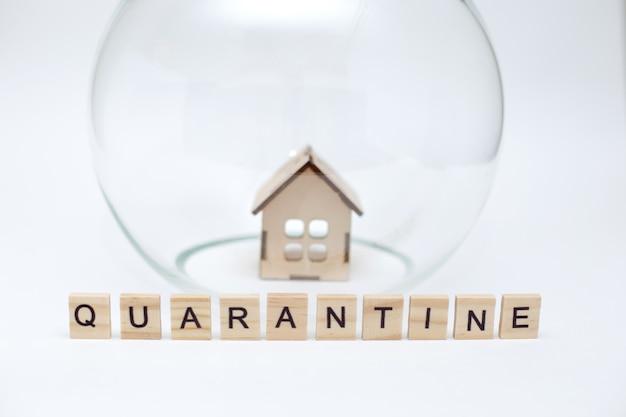 Model drewnianego domu pod szklaną kopułą i drewniane litery z napisem kwarantanna