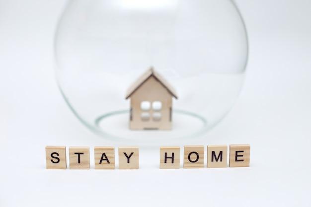 Model drewnianego domu pod szklaną kopułą i drewniane litery z napisem stay home