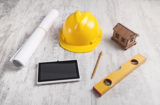 Model drewnianego domu z hełmem i tabletem.