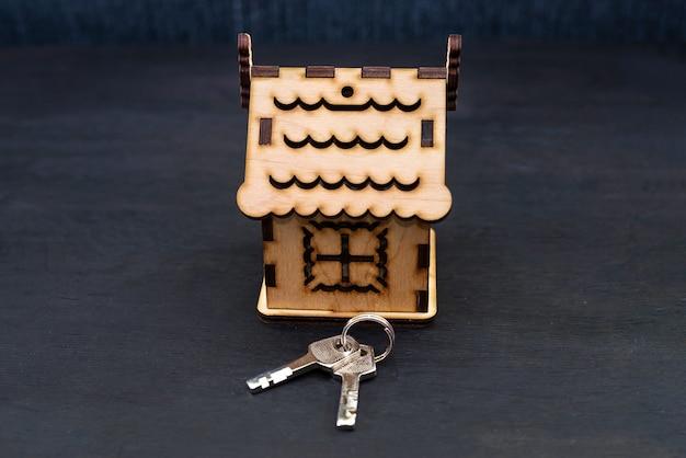 Model drewnianego domu z kluczami. budowanie, pożyczanie, kupowanie nieruchomości lub kupowanie nowego domu.