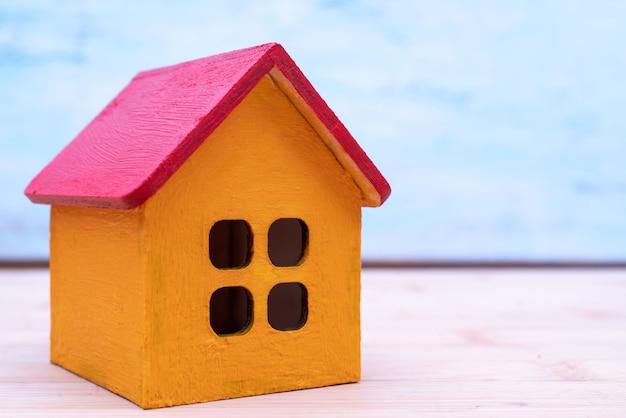 Model drewnianego żółtego domu z czerwonym dachem. wynajem i sprzedaż budynków i domków.