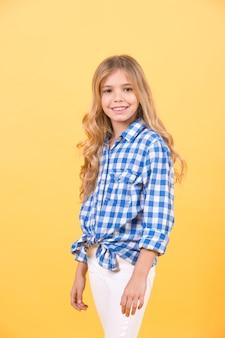Model dziecka uśmiech z długimi blond włosami. dziewczyna w niebieskiej koszuli w kratę na pomarańczowym tle. moda dziecięca, styl, trend. piękno, wygląd, fryzura. koncepcja szczęśliwego dzieciństwa.