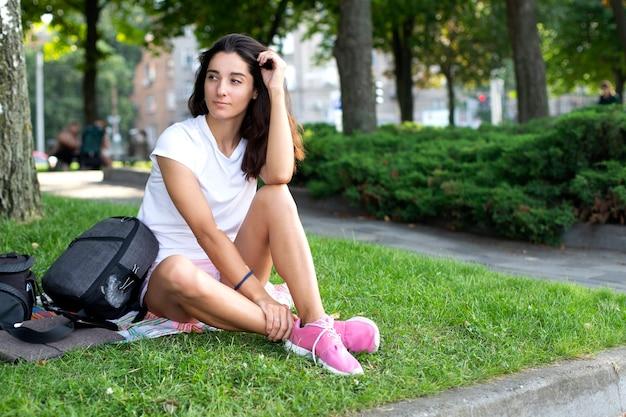 Model dziewczyna brnetka w białej koszuli i trampkach, siedzi na trawie w parku. niewyraźne tło, miejsce na napis.