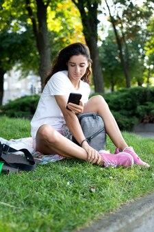 Model dziewczyna w białej koszuli i trampkach, z telefonem siedzi na trawie. rozmowy telefoniczne