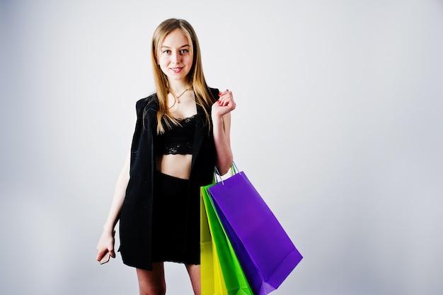 Model dziewczyna w czarnej odzieży z postawionymi kolorowe torby na zakupy