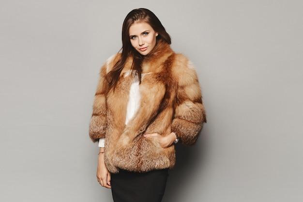 Model dziewczyna w luksusowe futro zimowe na szarym tle, na białym tle. moda zimowa.
