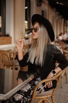 Model dziewczyna w okularach przeciwsłonecznych i czarnym kapeluszu, picie wina w kawiarni tabeli na ulicy, lato moda strzał.