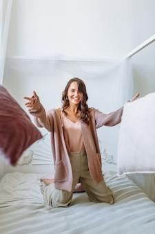 Model dziewczyna w rozciągniętej kurtce z dzianiny na łóżku. rzuć poduszki do przodu