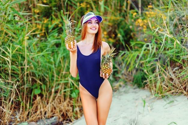 Model dziewczyny w monokini na brzegu morza na tropikalnej wyspie z dwoma ananasami