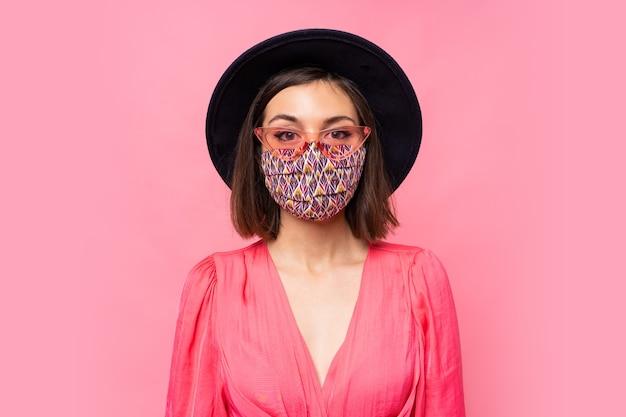 Model europejski ubrany w stylową maskę ochronną. nosi czarny kapelusz i okulary przeciwsłoneczne. pozowanie na różowej ścianie