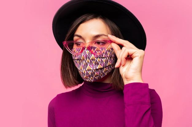 Model europejski ubrany w stylową maskę ochronną. nosi czarny kapelusz i okulary przeciwsłoneczne.