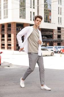 Model facet ze stylową fryzurą pozuje na zewnątrz w białej koszuli i szarych spodniach. modna fryzura spoczywa w pobliżu nowoczesnego centrum biznesowego. atrakcyjny facet na ulicy w letni dzień.