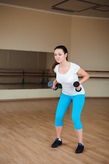 Model fitness robi trening kulturystyczny z ciężarami.