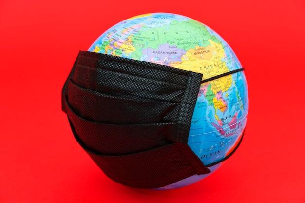 Model globu ziemskiego z czarną maską chirurgiczną na białym tle na czerwonym tle