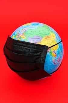 Model globu ziemskiego z czarną maską chirurgiczną na czerwonym tle