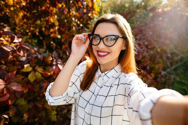 Model gougeus bierze selfie trzymając jej okulary jedną ręką w jesiennym ogrodzie.
