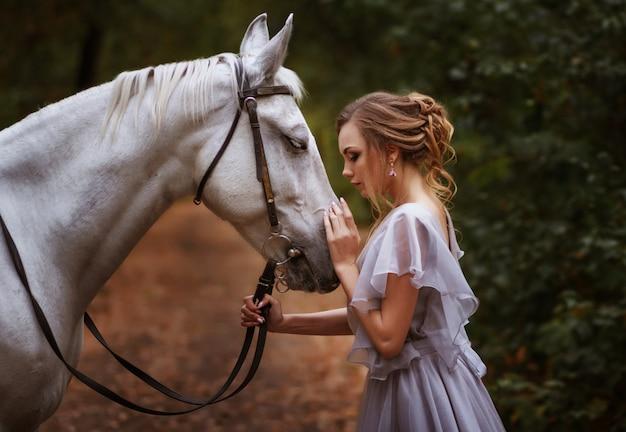 Model i biały koń patrzą na siebie. portret. tło zamazane, efekt artystyczny.