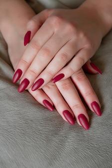 Model kobieta pokazując czerwony szelak manicure na długich paznokciach