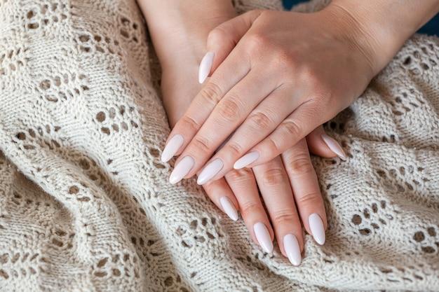 Model kobieta pokazując jasnoróżowy manicure nago szelakowy o