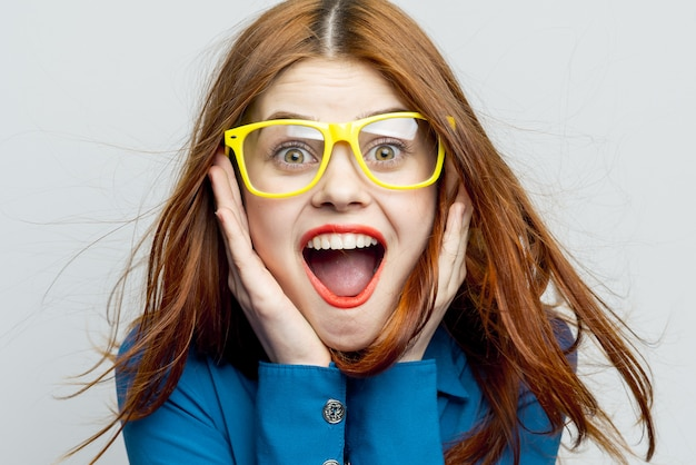 Model kobieta pozuje w okularach na jasnej ścianie, emocje