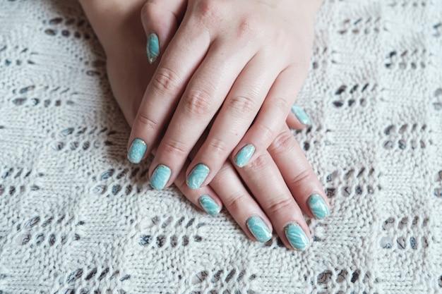 Model kobieta ręka pokazuje szelak marmurowy zielony pastelowy manicure ze złotym liściem na krótkich paznokciach