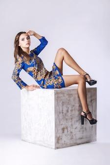 Model, kobieta w modnej sukience pełnej długości w studio na wewnętrznej kostce na jasnej ścianie