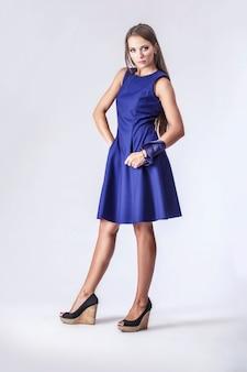 Model, kobieta w modnej sukience w pełnej długości w studio na jasnej ścianie