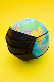 Model kuli ziemskiej z czarną maską chirurgiczną na białym tle