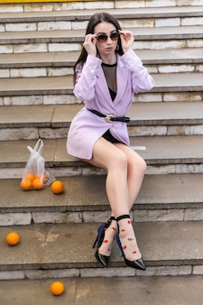 Model ładna kobieta moda z owocowymi pomarańczami siedzi na schodach w fioletową kurtkę, czarne buty.