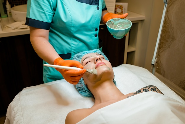 Model leżący na kanapie z zamkniętymi oczami. ręka w niebieskiej rękawiczce dotykająca twarzy pacjenta pędzelkiem