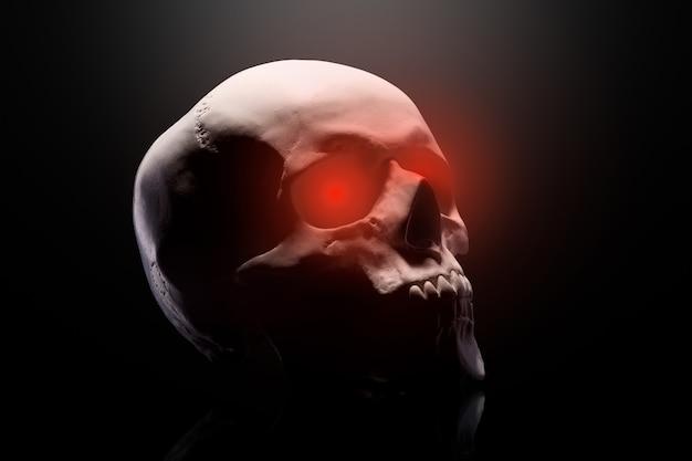 Model ludzkiej czaszki z czerwonymi oczami na czarnym tle