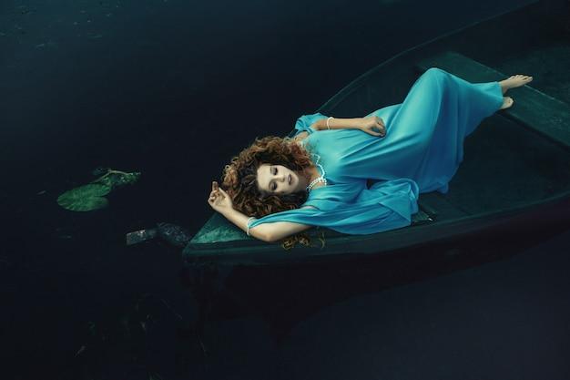 Model ma na sobie niebieską sukienkę pozuje w łodzi na wodzie