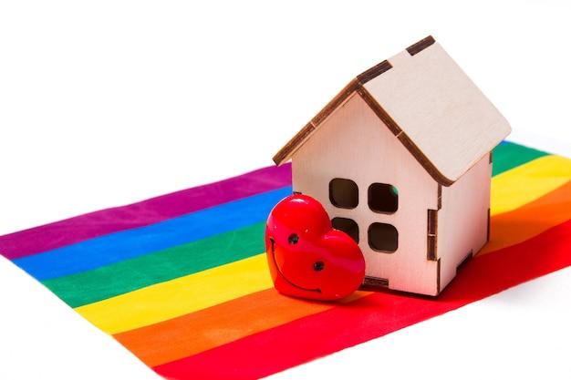 Model małego drewnianego domku i serduszko stoi na fladze kolorów tęczy
