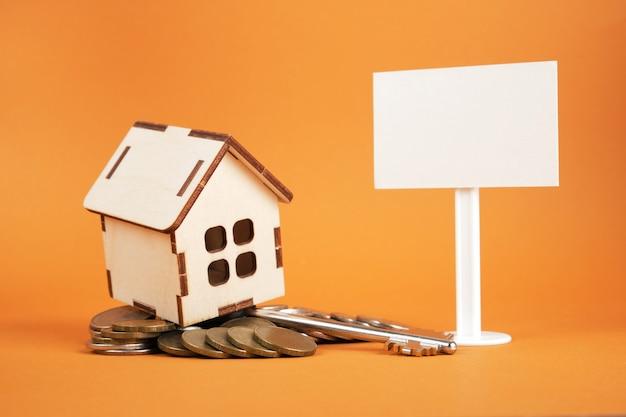 Model małego drewnianego domu, biały pusty znak i stos monet na brązowym tle