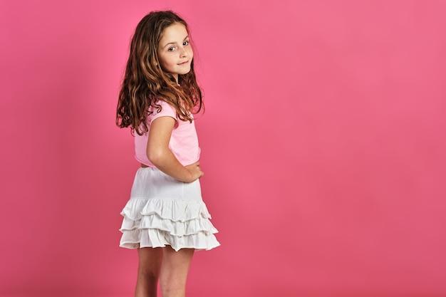 Model małej dziewczynki pozuje na różowej ścianie