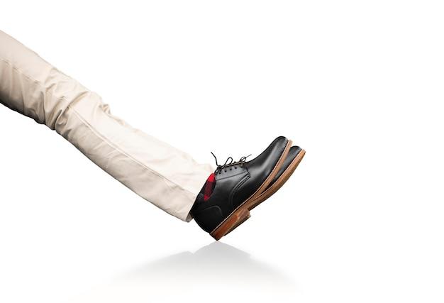 Model męski ubrany w spodnie i czarne skórzane buty.