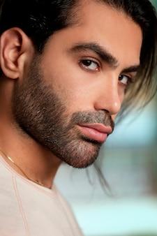 Model męski w białej koszulce i stylowej fryzurze
