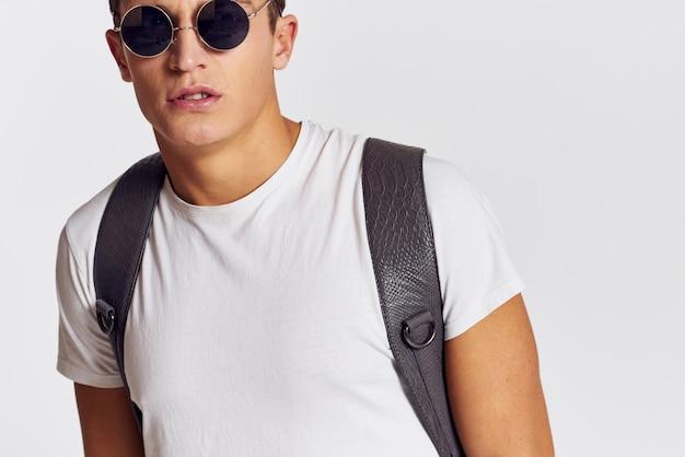 Model mężczyzna pozowanie w dżinsach i białej koszulce na jasnym tle